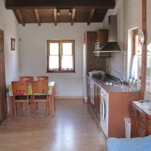vista de cocina con electrodomésticos y mesa